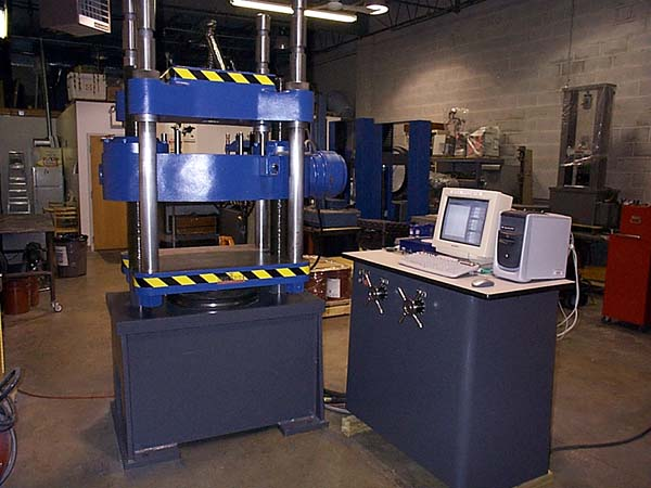 A 400,000 lb capacity manually operated Tinius Olsen Testing Machine retrofitted with ADMET's MTESTQuattro® Materials Testing System. MTESTQuattro features load, position, axial strain, transverse strain and auxillary input channels